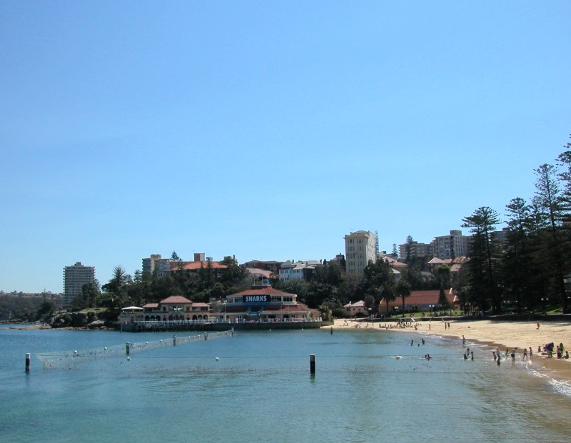 Beach next to Manly Wharf, with the Manly Sea Life Sanctuary (Aquarium) in the Background.