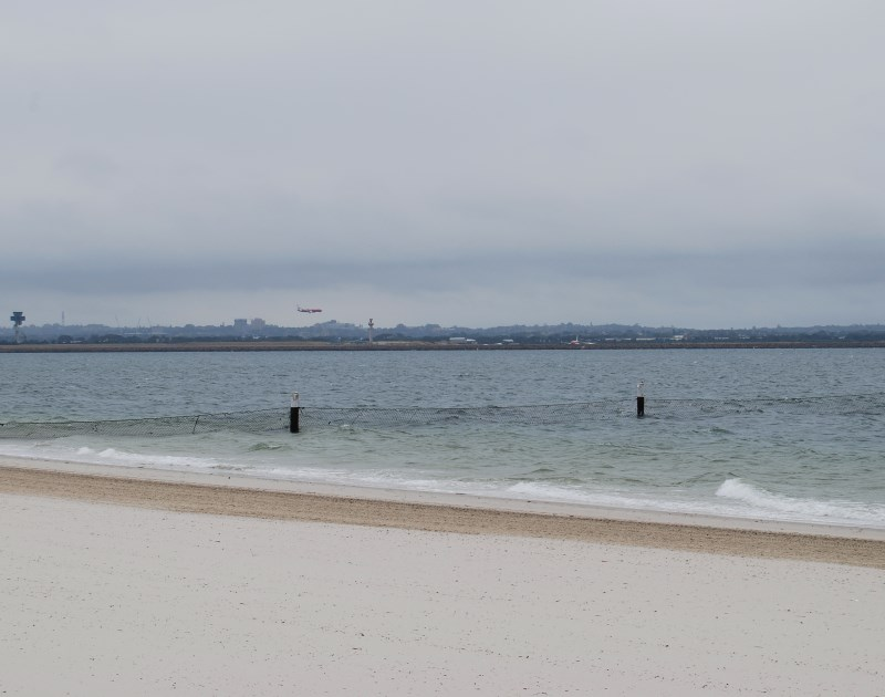 The wide Beach at Brighton le Sands, Botany Bay. Sydney Airport in the Distance